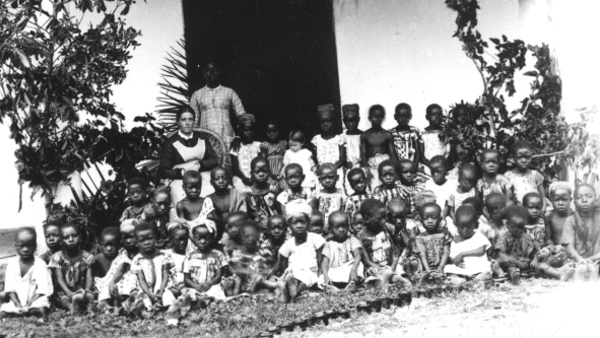 Fotografie. Děti z Basilejské misie s misionářkou a místní vychovatelkou před vchodem do školy. Ghana (Zlaté pobřeží), 1885-1888. Zdroj: Národní muzeum